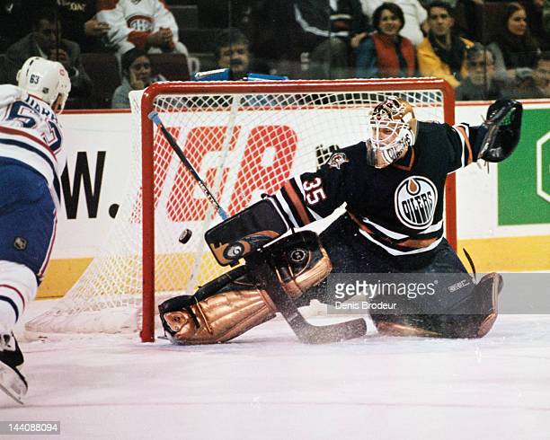 Tommy Salo of the Edmonton Oilers attempts to make a save on a shot by Craig Darby of the Montreal Canadiens Circa 2003 at the Bell Centre in...