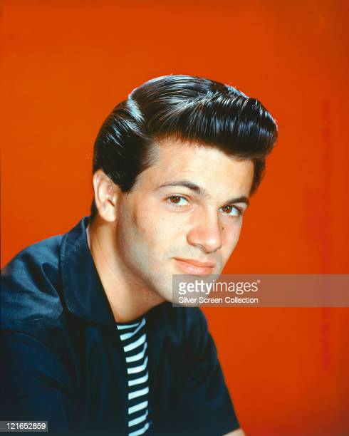 Tommy Sands US singer and actor wearing a dark blue jacket over a blackandwhite striped tshirt in a studio portrait against an orange background...
