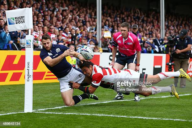 Tommy Seymour of Scotland is tackled by Ayumu Goromaru of Japan as he fails to go over for a try during the 2015 Rugby World Cup Pool B match between...