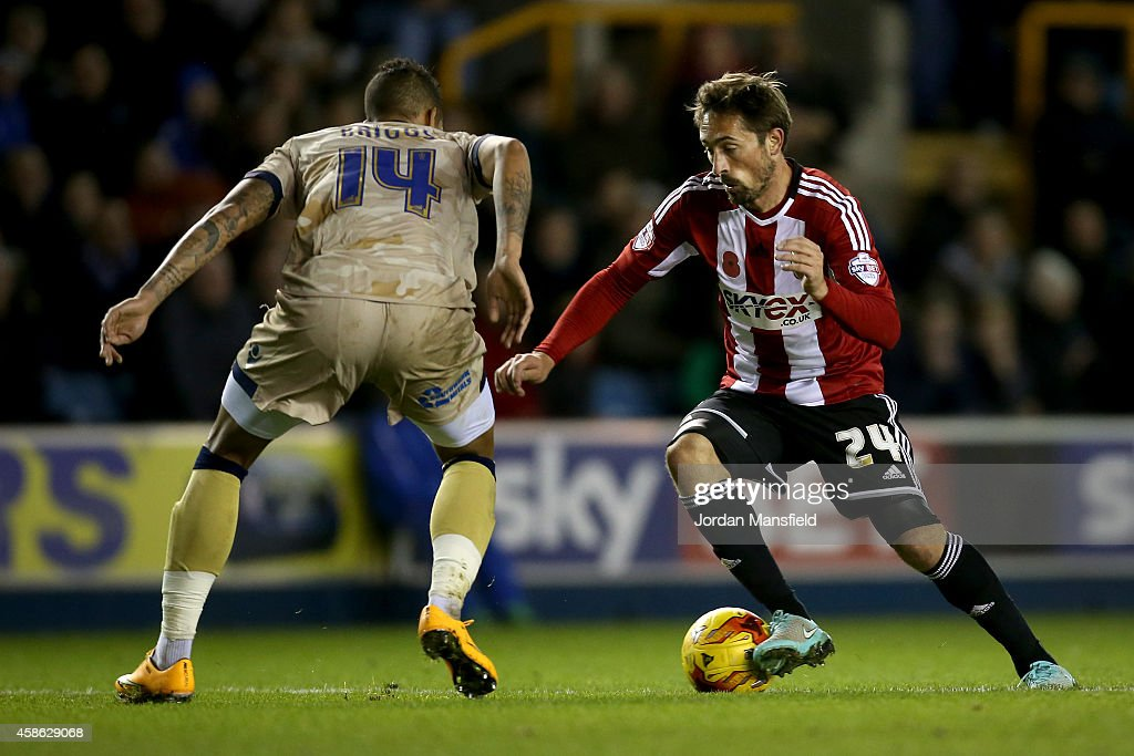 Tommy Smith of Brentford controls the ball under pressure from Matthew Briggs of Millwall during the Sky Bet Championship match between Millwall and Brentford at The Den on November 8, 2014 in London, England.