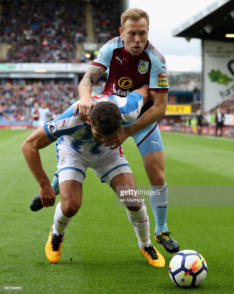Tommy Smith of Huddersfield Town controls the ball under pressure of Scott Arfield of Burnley during the Premier League match between Burnley and Huddersfield Town at Turf Moor on September 23, 2017 in Burnley, England.