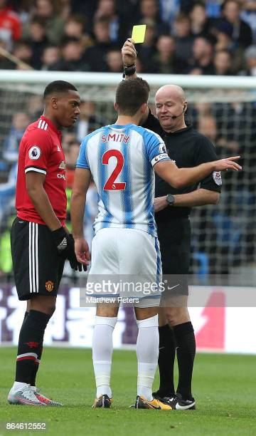 Tommy Smith of Huddersfield Town is booked by referee Lee Mason during the Premier League match between Huddersfield Town and Manchester United at...