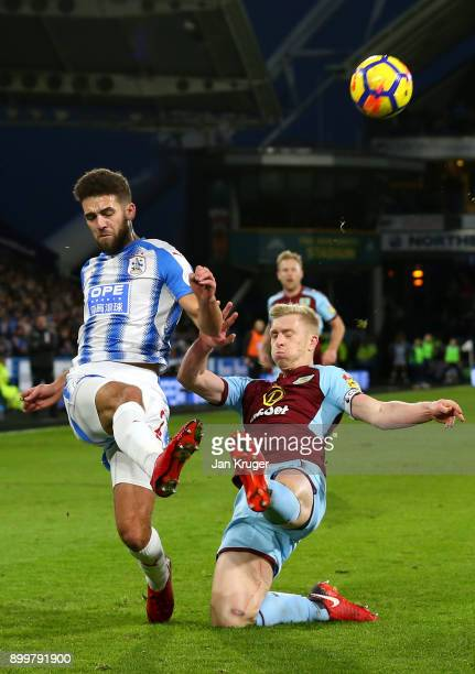 Tommy Smith of Huddersfield Town is challenged by Ben Mee of Burnley during the Premier League match between Huddersfield Town and Burnley at John...
