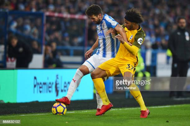 Tommy Smith of Huddersfield Town is challenged by Isaiah Brown of Brighton and Hove Albion during the Premier League match between Huddersfield Town...