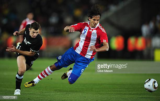 Tommy Smith of New Zealand tackles Roque Santa Cruz of Paraguay during the 2010 FIFA World Cup South Africa Group F match between Paraguay and New...