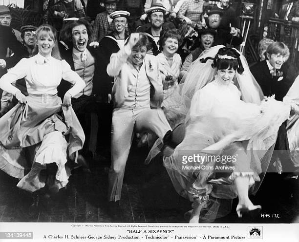 Tommy Steele and Julia Foster dancing among a group in a scene from the film 'Half A Sixpence', 1967.
