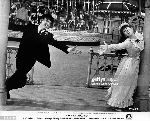 Tommy Steele and Julia Foster reaching out to each other in a scene from the film 'Half A Sixpence', 1967.
