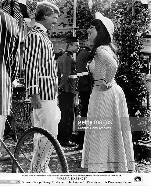 Tommy Steele and Julia Foster smiling as they look at each other in a scene from the film 'Half A Sixpence', 1967.