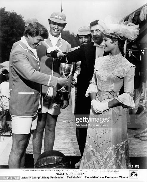Tommy Steele and Penelope Horner smile as champagne is poured into his trophy cup in a scene from the film 'Half A Sixpence' 1967