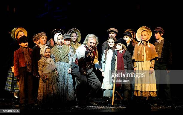 Tommy Steele as Ebenezer Scrooge with children from the company in Scrooge the Musical at the London Palladium