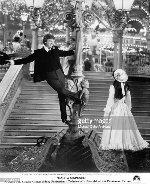 Tommy Steele dancing around street pole in front of Julia Foster in a scene from the film 'Half A Sixpence', 1967.