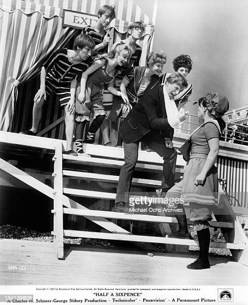 Tommy Steele on the steps and singing to Julia Foster in a scene from the film 'Half A Sixpence', 1967.