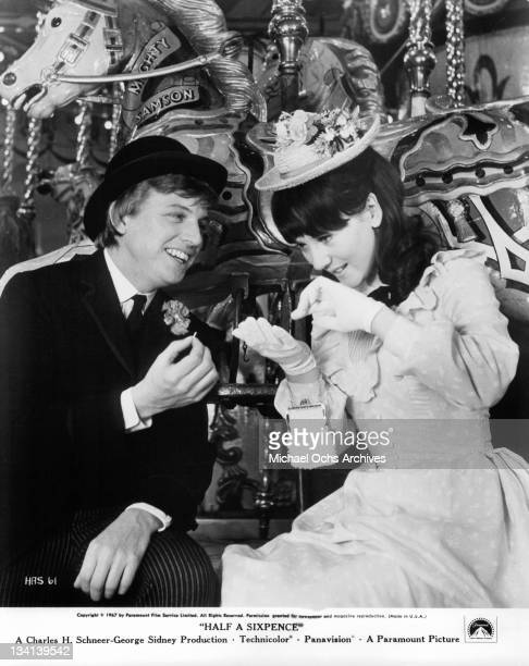 Tommy Steele smiles with Julia Foster as she looks into her glove in a scene from the film 'Half A Sixpence' 1967