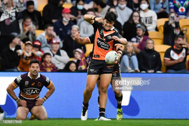 Tommy Talau of the Tigers celebrates scoring a try during the round 18 NRL match between the Brisbane Broncos and the Wests Tigers at Suncorp...