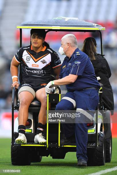 Tommy Talau of the Tigers is helped off the field during the round 25 NRL match between the Wests Tigers and the Canterbury Bulldogs at Moreton Daily...