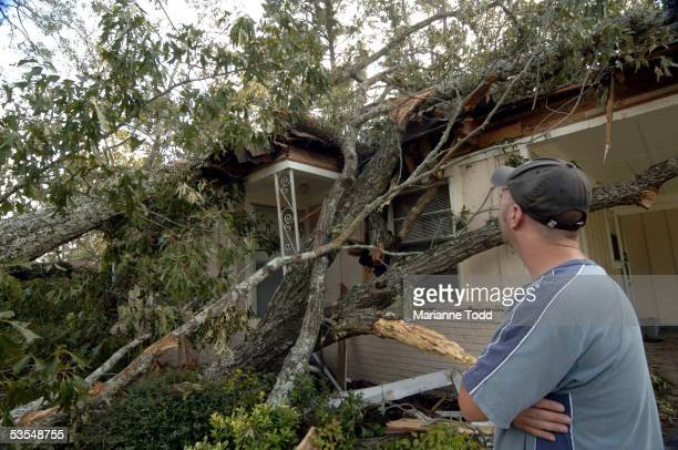 Tommy Townsend stands in front of his damaged home the day after Hurricane Katrina made her way inland August 30 2005 in Meridian Mississippi Gas...