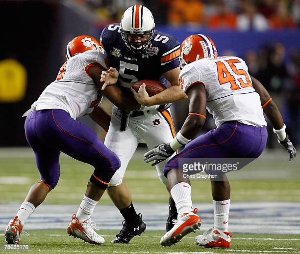 Tommy Trott of the Auburn University Tigers is tackled by Scotty Cooper and Cortney Vincent of the Clemson University Tigers during the ChickFilA...