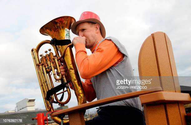 Tommy Tuba sits a top a lifeguard chair and calls everyone to line up before the annual L Street Brownies New Year's Day Plunge at the Curley...