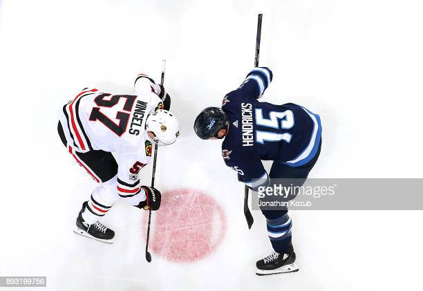 Tommy Wingels of the Chicago Blackhawks and Matt Hendricks of the Winnipeg Jets get set for a second period faceoff at the Bell MTS Place on December...