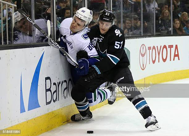 Tommy Wingels of the San Jose Sharks checks Nikita Tryamkin of the Vancouver Canucks at SAP Center on March 31 2016 in San Jose California
