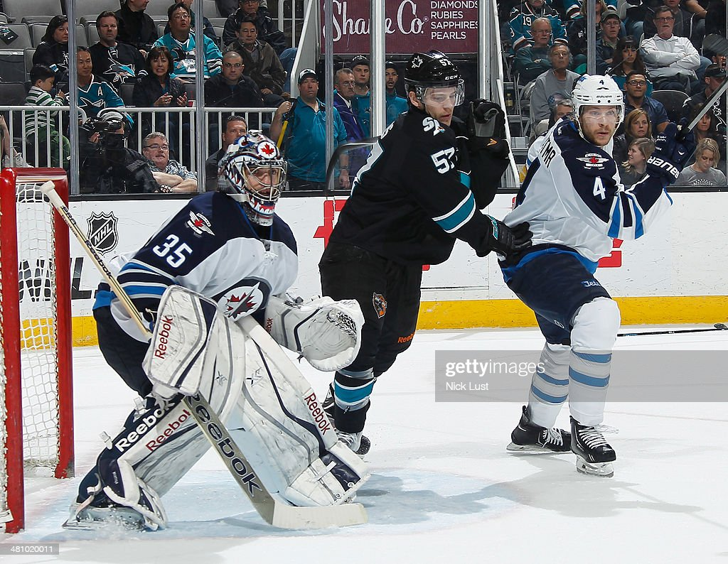 Tommy Wingels #57 of the San Jose Sharks crashes the net against Al Montoya #35 and Paul Postma #4 of the Winnipeg Jets during an NHL game on March 27, 2014 at SAP Center in San Jose, California.