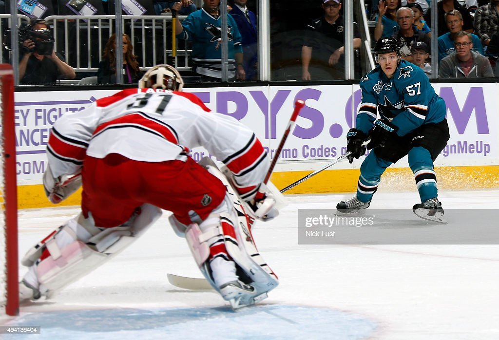 Tommy Wingels #57 of the San Jose Sharks sets up for a shot on net against Eddie Lack #31 of the Carolina Hurricanes during a NHL game at the SAP Center at San Jose on October 24, 2015 in San Jose, California.