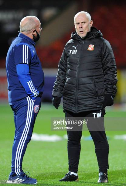 Tommy Wright, First Team Coach of Swindon Town speaks with an Accrington Stanley member of staff on the pitch prior to the Sky Bet League One match...