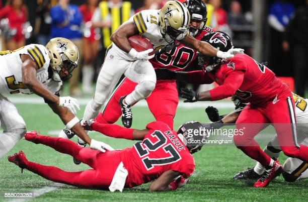 Tommylee Lewis of the New Orleans Saints carries the ball against Damontae Kazee and Derrick Coleman of the Atlanta Falcons at MercedesBenz Stadium...