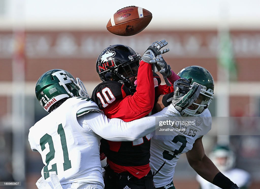 Tommylee Lewis #10 of the Northern Illinois Huskies looses control of the ball as he is hit by Ja'Ron Gillespie #21 (L) and Donald Coleman #3 of the Eastern Michigan Eagles at Brigham Field on October 26, 2013 in DeKalb, Illinois.