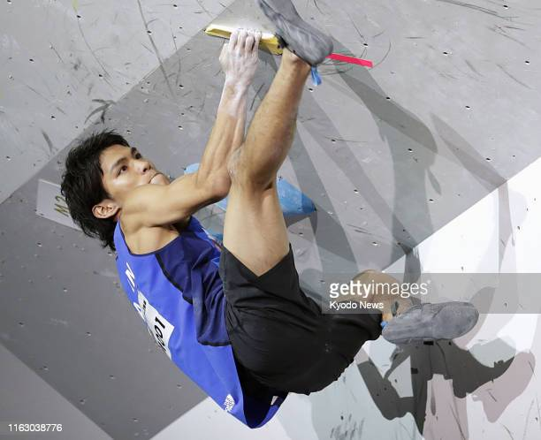 Tomoa Narasaki of Japan competes in the bouldering discipline of the men's combined final at the sport climbing world championships in Hachioji...