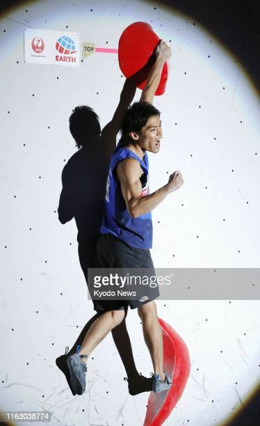 Tomoa Narasaki of Japan reacts after completing all three problems in the bouldering discipline of the men's combined final at the sport climbing...