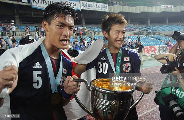 Tomoaki Makino and Yoichiro Kakitani of Japan celebrate with the trophy after winning the EAFF East Asian Cup 2013 against South Korea at Jamsil...