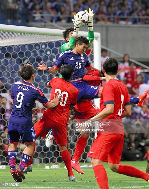 Tomoaki Makino of Japan and Mohamad Izwan Bin Mahbud of Singapore compete for the ball during the 2018 FIFA World Cup Asian Qualifier second round...