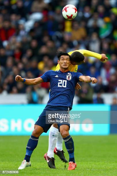 Tomoaki Makino of Japan and Paulinho of Brazil in action during the international friendly match between Brazil and Japan at Stade PierreMauroy on...