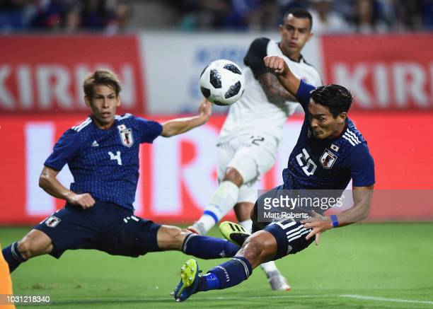 Tomoaki Makino of Japan attempts to block a shot on goal by Randall Leal of Costa Rica during the international friendly match between Japan and...