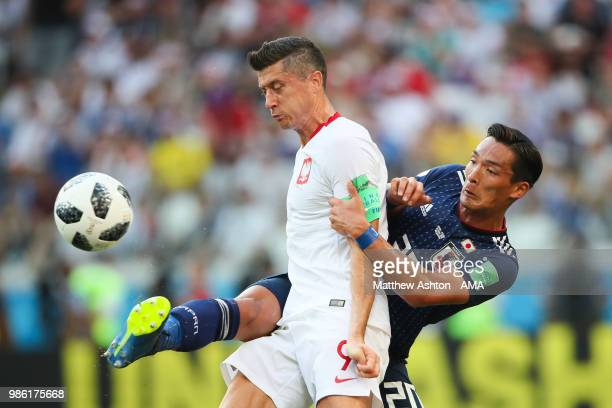 Tomoaki Makino of Japan battles for the ball with Robert Lewandowski of Poland during the 2018 FIFA World Cup Russia group H match between Japan and...