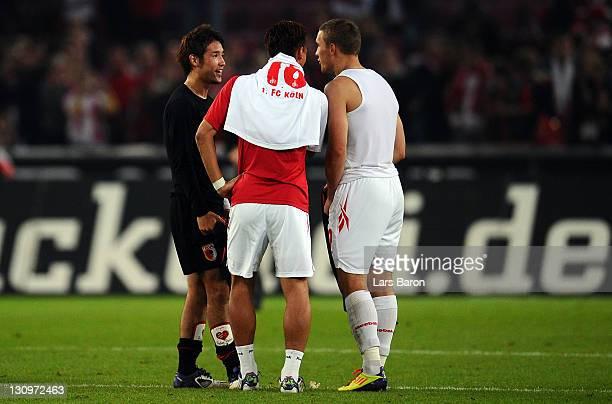 Tomoaki Makino of Koeln is seen with Hajime Hosogai of Wolfsburg and team mate Lukas Podolski after the Bundesliga match between 1 FC Koeln and FC...