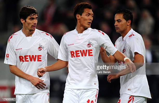 Tomoaki Makino of Koeln is seen with team mates Henrique Sereno and Ammar Jemal during the Bundesliga match between 1 FC Koeln and Hannover 96 at...