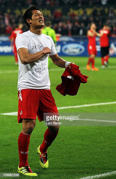 Tomoaki Makino of Koeln shows a shirt for the victims of the earthquake in his home country Japan after winning the Bundesliga match between 1 FC...