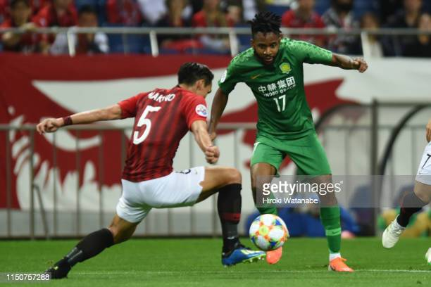 Tomoaki Makino of Urawa Red Diamonds and Cedric Bakambu of Beijing Guoan compete for the ball during the AFC Champions League Group G match between...