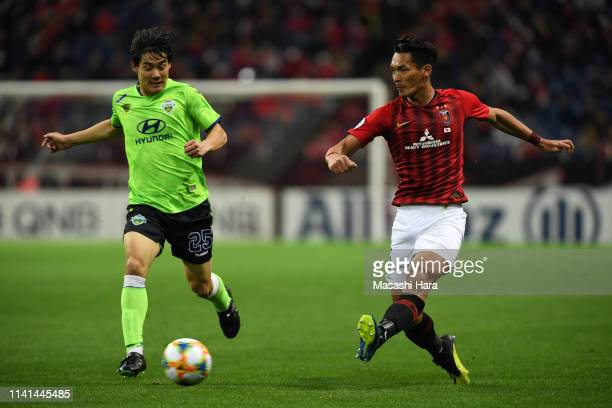 Tomoaki Makino of Urawa Red Diamonds and Choi Chulsoon of Jeonbuk Hyundai Motors compete for the ball during the AFC Champions League Group G match...