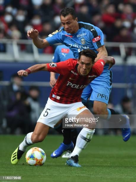 Tomoaki Makino of Urawa Red Diamonds and Leandro Damiao of Kawasaki Frontale compete for the ball during the Fuji Xerox Super Cup between Kawasaki...