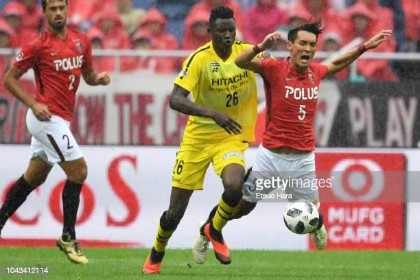 Tomoaki Makino of Urawa Red Diamonds and Olunga of Kashiwa Reysol compete for the ball during the JLeague J1 match between Urawa Red Diamonds and...