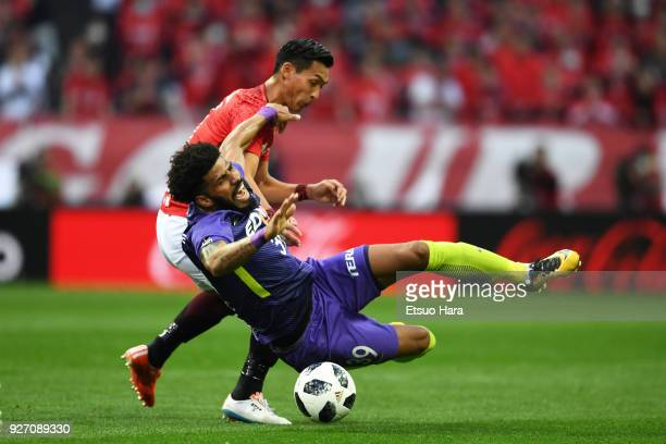 Tomoaki Makino of Urawa Red Diamonds and Patric of Sanfrecce Hiroshima compete for the ball during the JLeague J1 match between Urawa Red Diamonds...