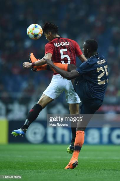 Tomoaki Makino of Urawa Red Diamonds competes for the ball against Modibo Maiga of Buriram United during the AFC Champions League Group G match...