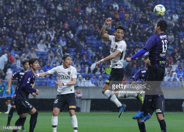Tomoaki Makino of Urawa Reds and Kim Young Gown of Gamba Osaka attempt header in front of the Oh Jae Suk of Gamba Osaka compete for the ball during...