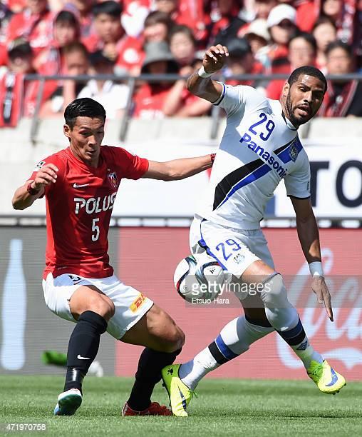 Tomoaki Makino of Urawa Reds and Patric of Gamba Osaka compete for the ball during the J.League match between Urawa Red Diamonds and Gamba Osaka at...