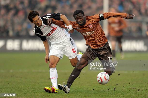 Tomoaki Maskino of Koeln and Gerald Asamoah of Pauli battle for the ball during the Bundesliga match between FC St Pauli and 1 FC Koeln at Millerntor...