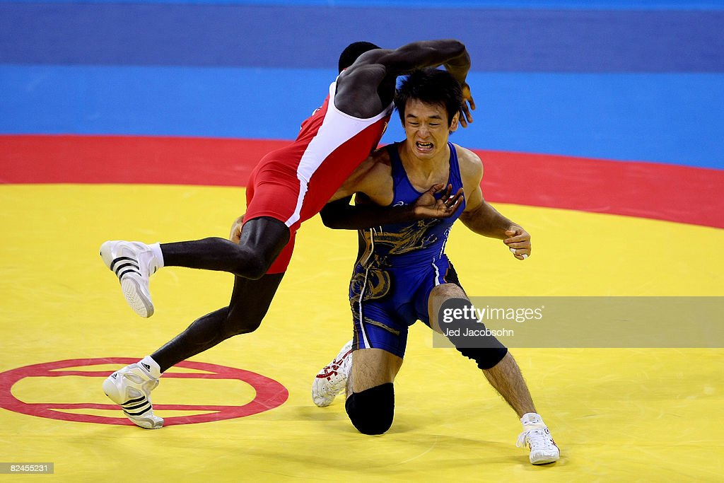 Tomohiro Matsunaga (blue) of Japan competes against Adama Diatta of Senegal in the 55 kg freestylewrestling event at the China Agriculture University Gymnasium on Day 11 of the Beijing 2008 Olympic Games on August 19, 2008 in Beijing, China.