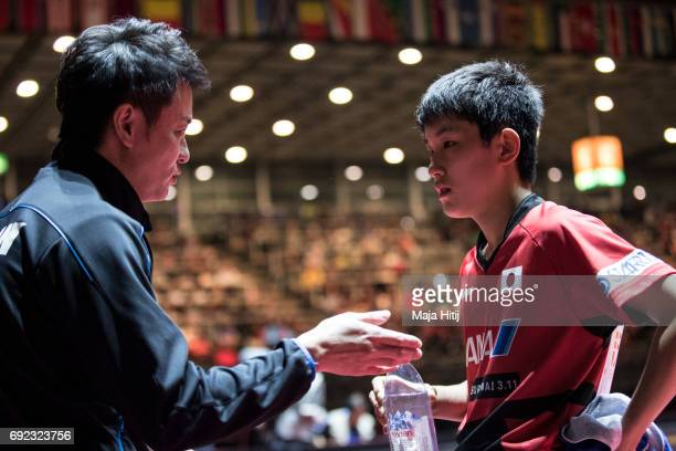 Tomokazu Harimoto of Japan talks to the coach during Men's Singles quarter Final at Table Tennis World Championship at at Messe Duesseldorf on June 4...